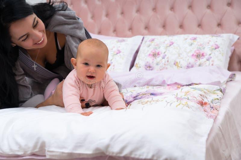 美丽的年轻母亲和她的婴孩在床上 免版税库存图片