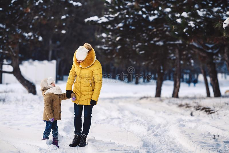 美丽的年轻母亲和她的小女儿在冬天森林里走握手 库存图片
