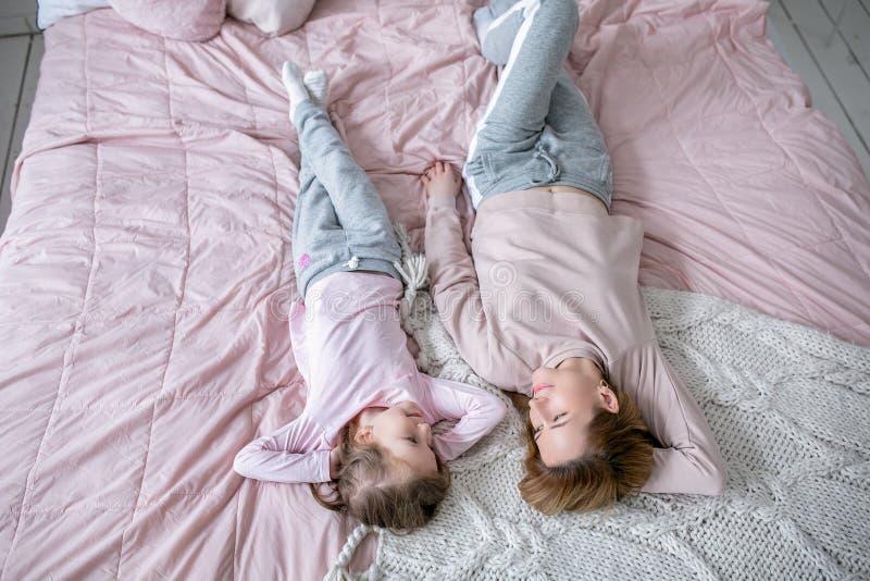 美丽的年轻母亲和她的小女儿在床上一起说谎在卧室,演奏,拥抱并且获得乐趣 库存图片