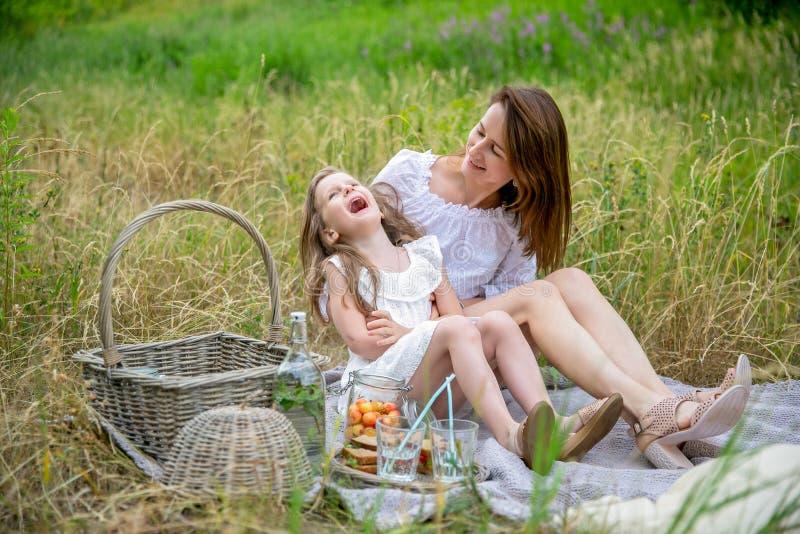 美丽的年轻母亲和她的小女儿白色礼服的获得乐趣在一顿野餐在一个夏日 他们坐地毯和 免版税图库摄影