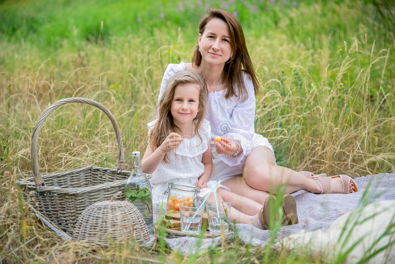 美丽的年轻母亲和她的小女儿白色礼服的获得乐趣在一顿野餐在一个夏日 他们坐毯子和 免版税库存照片