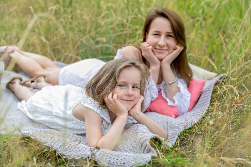 美丽的年轻母亲和她的小女儿白色礼服的获得乐趣在野餐 他们在草的格子花呢披肩说谎和 免版税库存照片