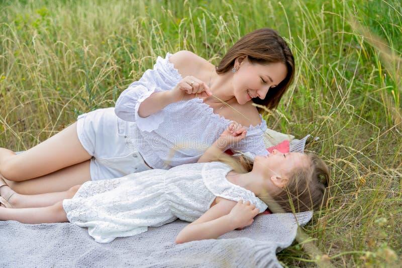 美丽的年轻母亲和她的小女儿白色礼服的获得乐趣在野餐 他们在草的格子花呢披肩说谎和 库存照片