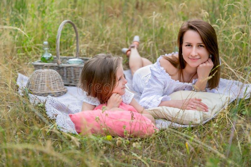 美丽的年轻母亲和她的小女儿白色礼服的获得乐趣在野餐 他们在草的格子花呢披肩说谎和 免版税图库摄影