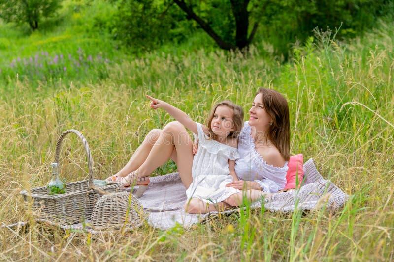 美丽的年轻母亲和她的小女儿白色礼服的获得乐趣在野餐 他们坐在草的格子花呢披肩和 免版税库存照片