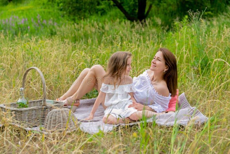 美丽的年轻母亲和她的小女儿白色礼服的获得乐趣在野餐 他们坐在草的格子花呢披肩和 免版税图库摄影