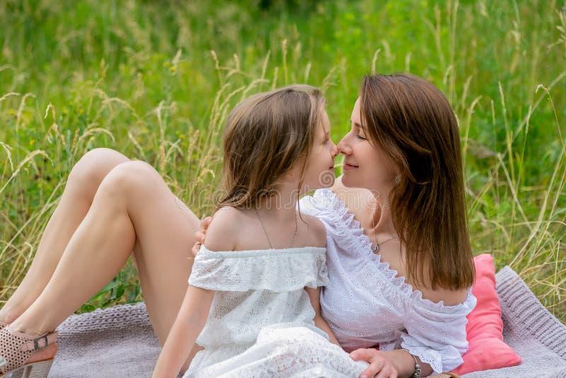 美丽的年轻母亲和她的小女儿白色礼服的获得乐趣在野餐 他们坐在草的格子花呢披肩和 库存图片