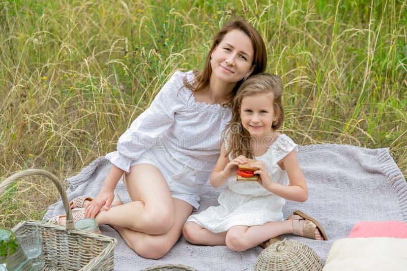 美丽的年轻母亲和她的小女儿白色礼服的获得乐趣在野餐 他们坐在草的格子花呢披肩和 免版税库存图片