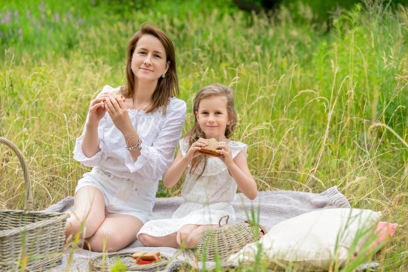美丽的年轻母亲和她的小女儿白色礼服的获得乐趣在野餐 他们坐在草的格子花呢披肩, 库存照片