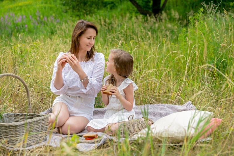 美丽的年轻母亲和她的小女儿白色礼服的获得乐趣在野餐 他们坐在草的格子花呢披肩, 库存图片