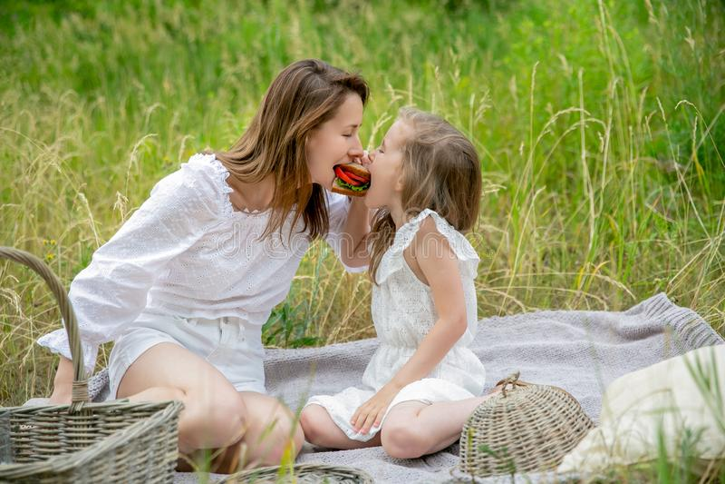 美丽的年轻母亲和她的小女儿白色礼服的获得乐趣在野餐 他们坐在草的格子花呢披肩, 免版税库存图片