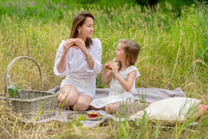 美丽的年轻母亲和她的小女儿白色礼服的获得乐趣在野餐 他们坐在草的格子花呢披肩, 免版税图库摄影
