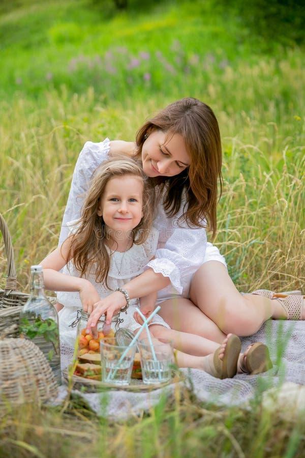 美丽的年轻母亲和她的小女儿白色礼服的获得乐趣在野餐 他们坐地毯并且带莓果出去 库存照片