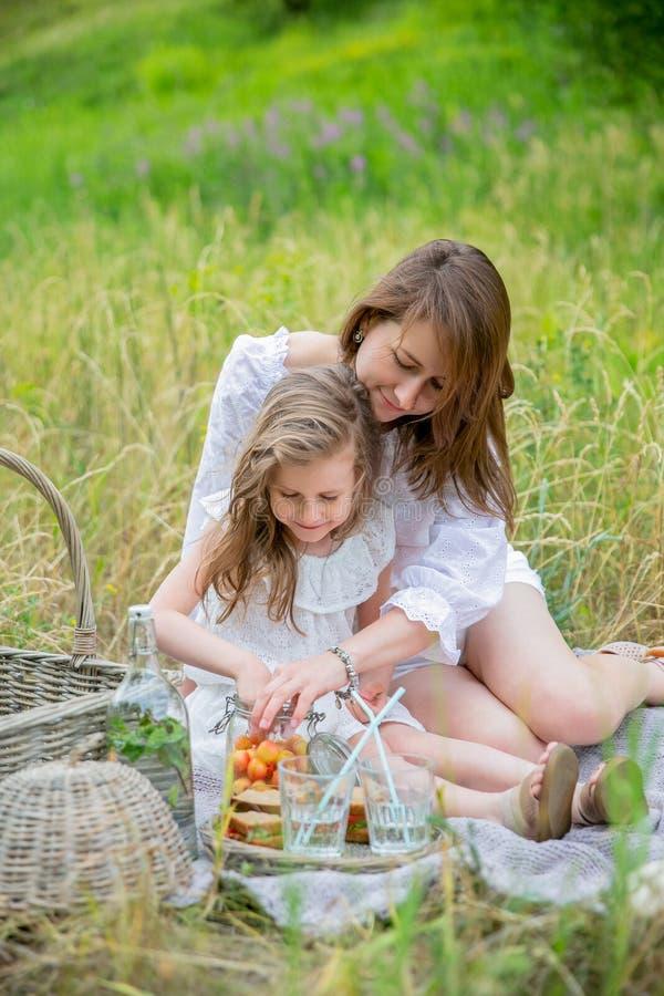 美丽的年轻母亲和她的小女儿白色礼服的获得乐趣在野餐 他们坐地毯并且带莓果出去 免版税库存照片