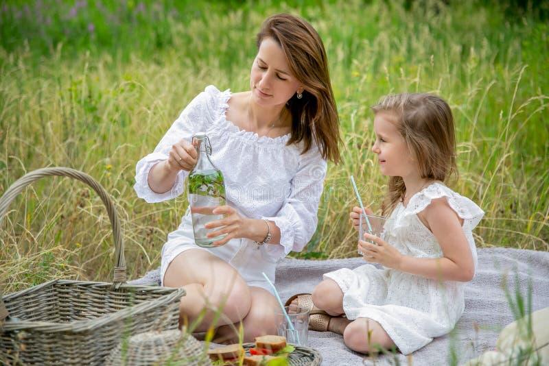 美丽的年轻母亲和她的小女儿白色礼服的获得乐趣在野餐 他们坐格子花呢披肩,并且妈妈打开 免版税库存照片