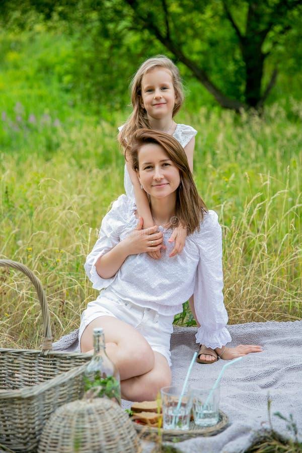 美丽的年轻母亲和她的小女儿白色礼服的获得乐趣在野餐 他们坐格子花呢披肩,拥抱和 免版税图库摄影
