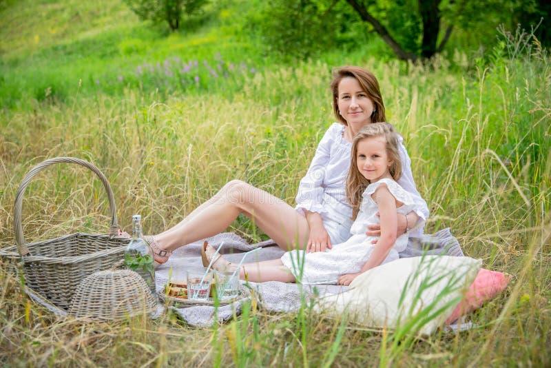美丽的年轻母亲和她的小女儿白色礼服的获得乐趣在野餐 他们坐格子花呢披肩,拥抱和 库存图片