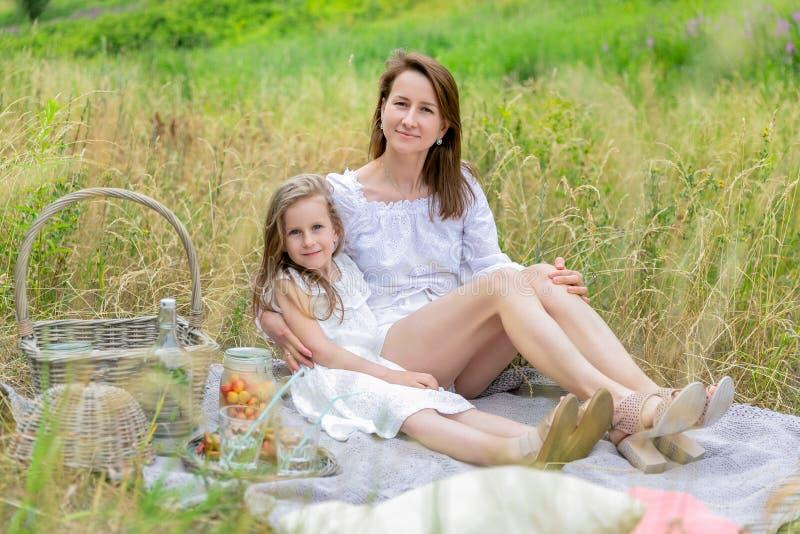 美丽的年轻母亲和她的小女儿白色礼服的获得乐趣在野餐 他们坐格子花呢披肩,拥抱和 免版税库存图片