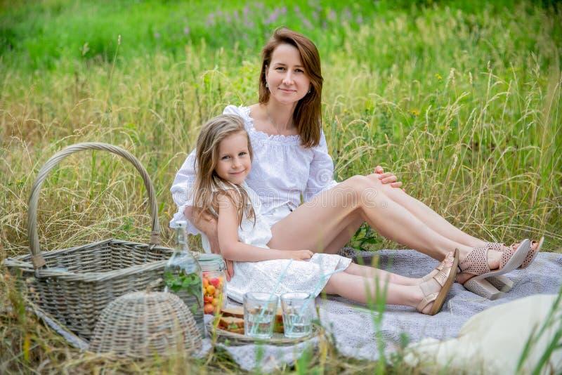美丽的年轻母亲和她的小女儿白色礼服的获得乐趣在野餐 他们坐格子花呢披肩,拥抱和 库存照片