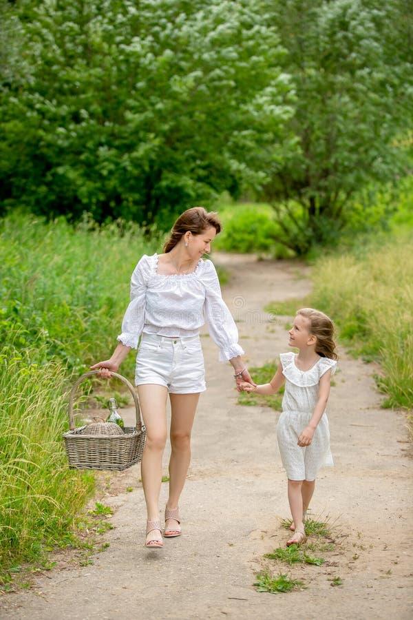 美丽的年轻母亲和她的小女儿白色礼服的获得乐趣在野餐 他们握手并且看彼此,步行 免版税库存照片