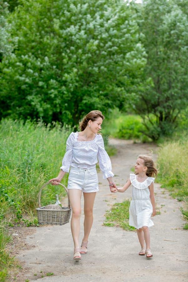 美丽的年轻母亲和她的小女儿白色礼服的获得乐趣在野餐 他们握手并且看彼此,步行 库存图片