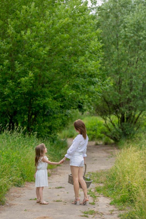 美丽的年轻母亲和她的小女儿白色礼服的获得乐趣在野餐 他们沿路走在公园 库存照片