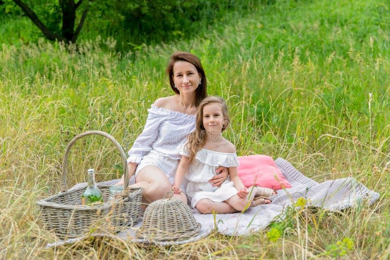 美丽的年轻母亲和她的小女儿白色礼服的获得乐趣在野餐 E r 库存图片