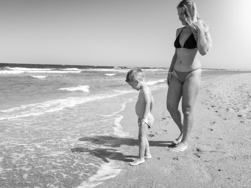 美丽的年轻母亲的黑白图象有她的小男孩儿童身分的在海滩的温暖的海波浪 免版税库存照片