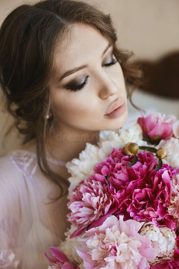 美丽的年轻深色的妇女画象有闭合的眼睛和大诱人的嘴唇的,有花花束的在她的手上 免版税库存图片
