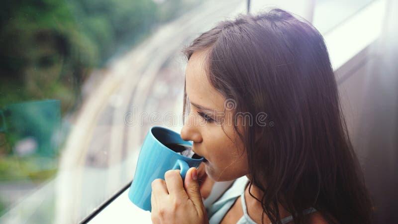 美丽的年轻深色的由全景窗口的妇女饮用的咖啡有令人惊讶的城市视图 库存照片