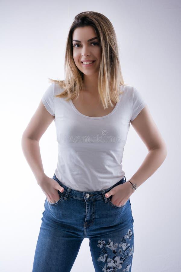 美丽的年轻白种人学生女孩画象有愉快的牙的微笑在蓝色牛仔裤和手的头发在口袋 免版税库存图片