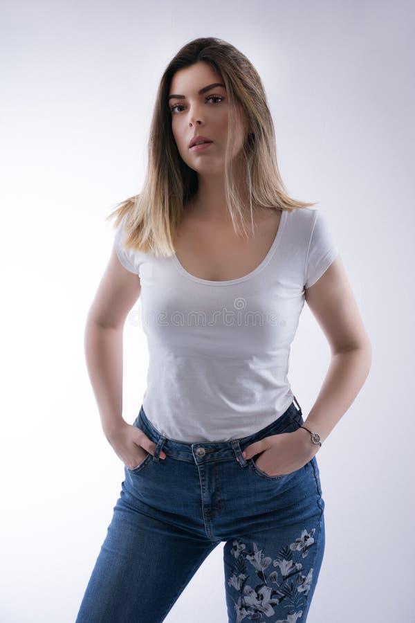 美丽的年轻白种人学生女孩画象有金发的在白色T恤杉和蓝色牛仔裤 免版税图库摄影