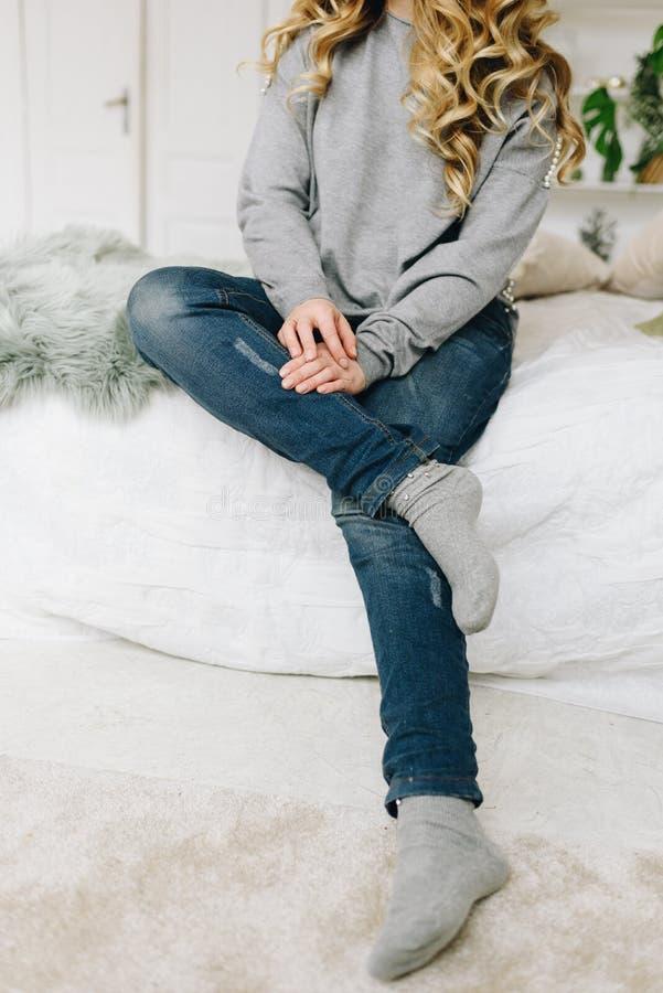 美丽的年轻白种人欧洲妇女偶然地坐床 免版税库存照片