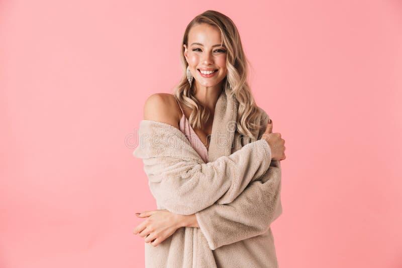 美丽的年轻白肤金发的妇女佩带的冬天毛皮大衣 免版税库存照片