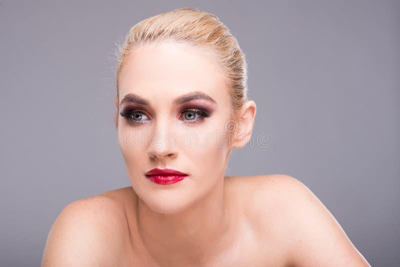 美丽的年轻白肤金发的妇女佩带的魅力构成 免版税库存图片