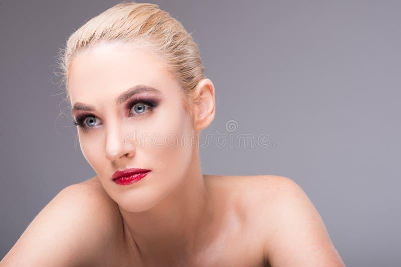 美丽的年轻白肤金发的妇女佩带的魅力构成 免版税图库摄影