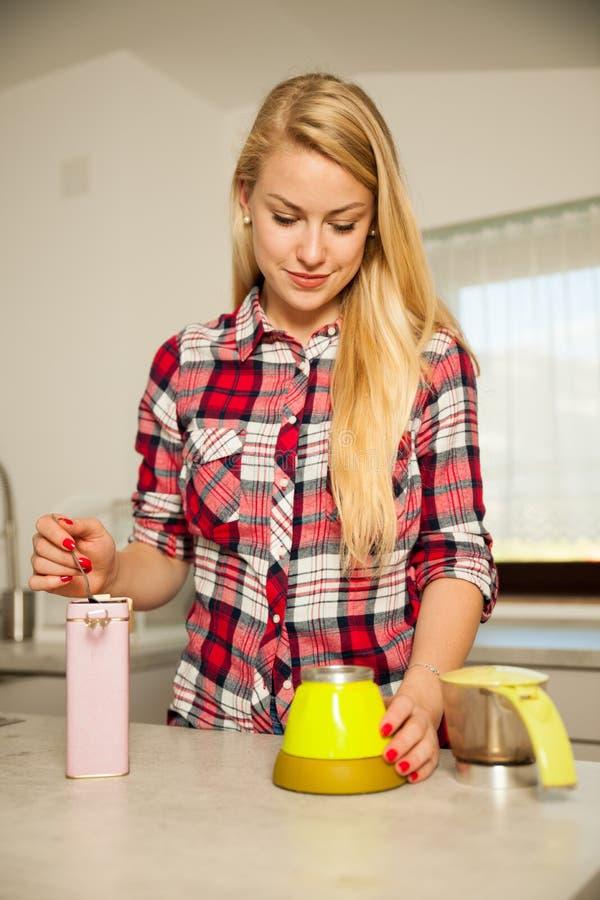 美丽的年轻白肤金发的妇女在厨房里烹调咖啡 免版税库存照片
