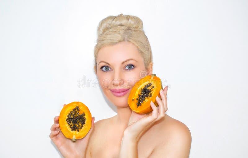 美丽的年轻白肤金发的妇女用番木瓜在手上 健康皮肤和润湿的概念 果子的好处 免版税库存照片