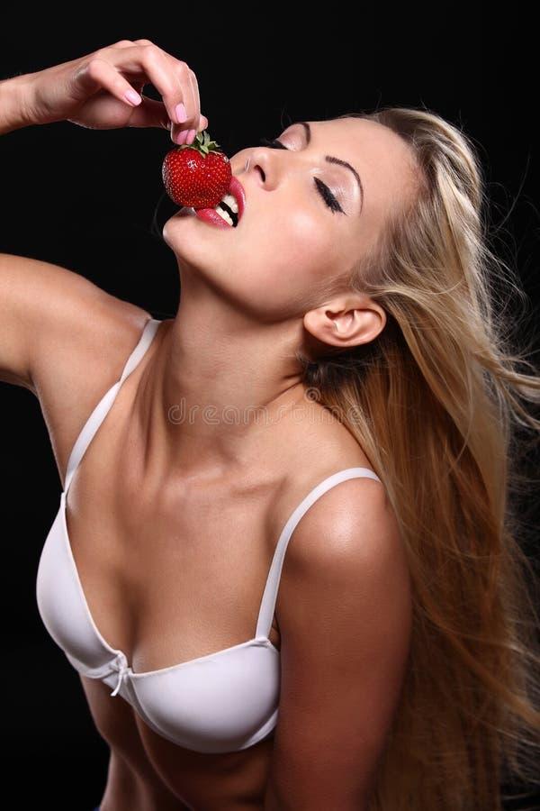 美丽的年轻白肤金发的妇女用草莓 免版税库存图片