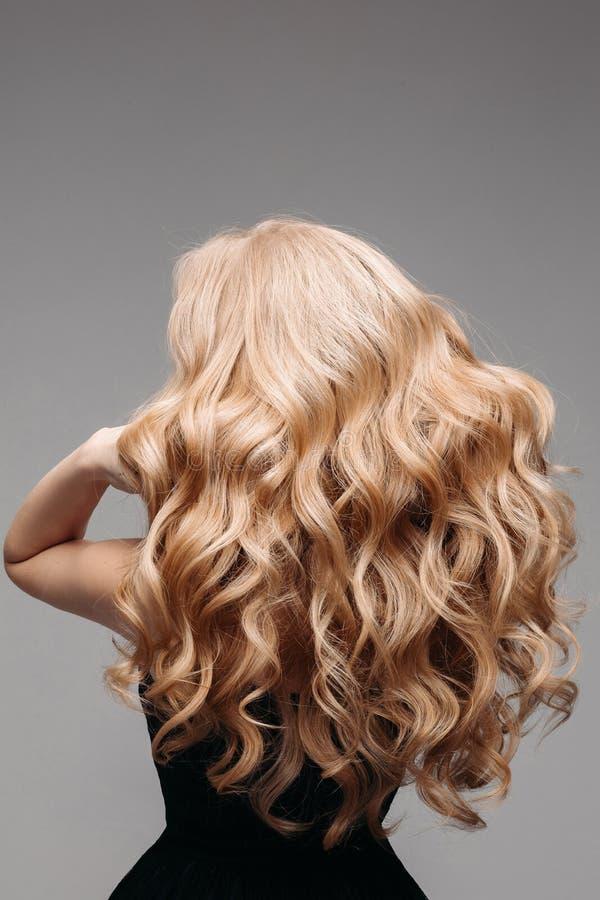 美丽的年轻白肤金发的妇女画象有长的波浪发的 回到视图 免版税库存图片