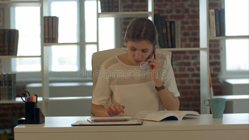美丽的年轻白肤金发的妇女谈话在手机和阅读书 免版税库存照片