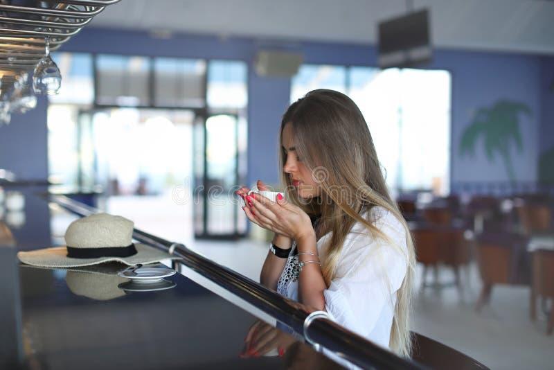 美丽的年轻白肤金发的饮用的咖啡 坐在咖啡馆的可爱的女孩 ?? ?? o 免版税图库摄影