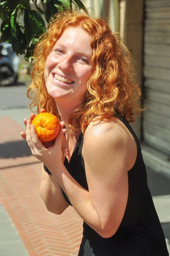 美丽的年轻红发妇女,在手在春天愉快地保留一个自被采摘的桔子在利古里亚意大利在度假 库存照片