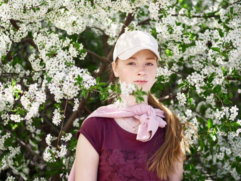 美丽的年轻红头发人妇女在开花的庭院里 接近的纵向 免版税图库摄影