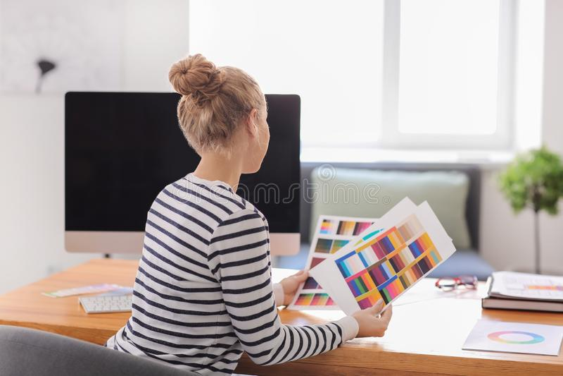 美丽的年轻设计师与色板显示一起使用在办公室 库存图片