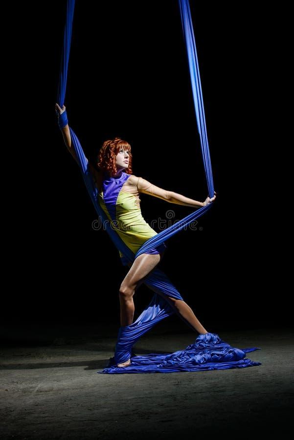 美丽的年轻运动女孩,在光的蓝色空中丝绸在黑暗中 库存照片