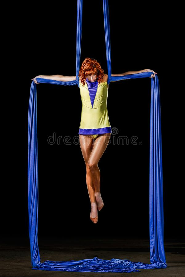 美丽的年轻运动性感的妇女,有红头发人的专业空中马戏艺术家在黄色服装在天空中做十字架 图库摄影