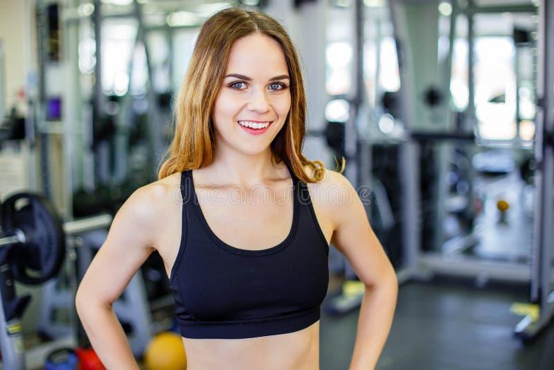 美丽的年轻运动的妇女 健身在体育俱乐部的女孩训练用锻炼设备 微笑和看照相机的妇女 免版税库存照片