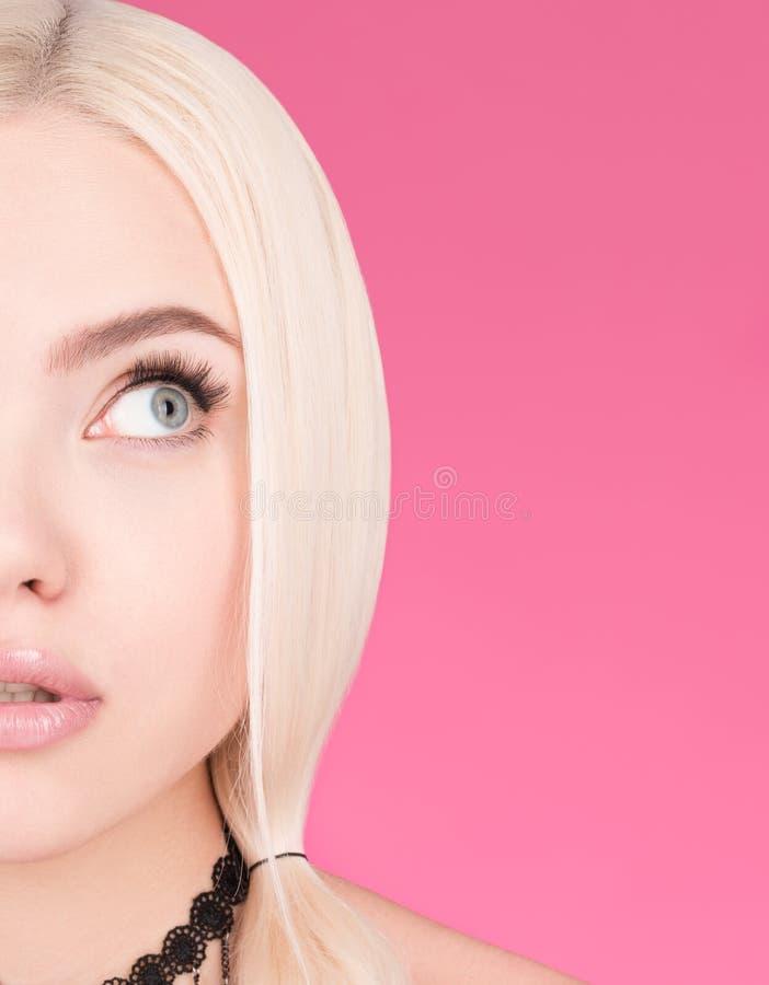 美丽的年轻金发碧眼的女人和自由空间的半面孔 看对边 免版税库存照片