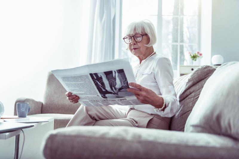 美丽的年长妇女读书报纸,当在家时等待丈夫 库存图片